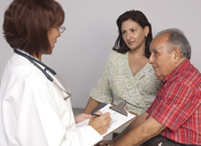 doctor talking to elderly person and caregiver