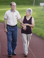 caregiver helps elderly man walk outdoors